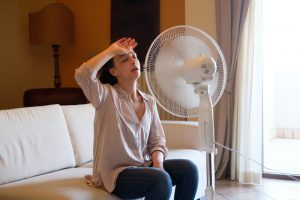 woman-sitting-on-couch-in-front-of-fan-looking-very-hot