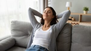 woman-leaning-back-on-couch-with-eyes-closed-and-smiling